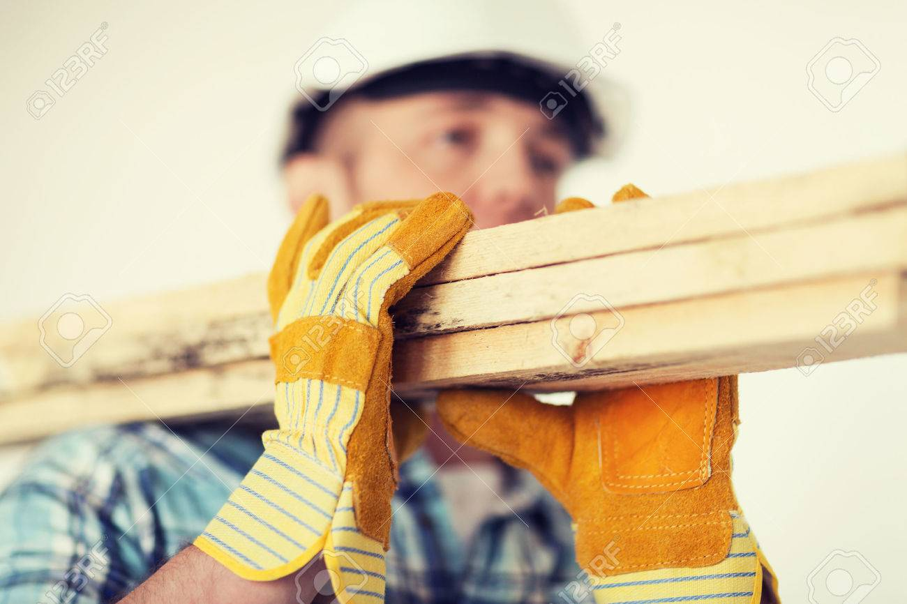 repair, building and home concept - close up of male in gloves and helmet carrying wooden boards on shoulder - 37681283