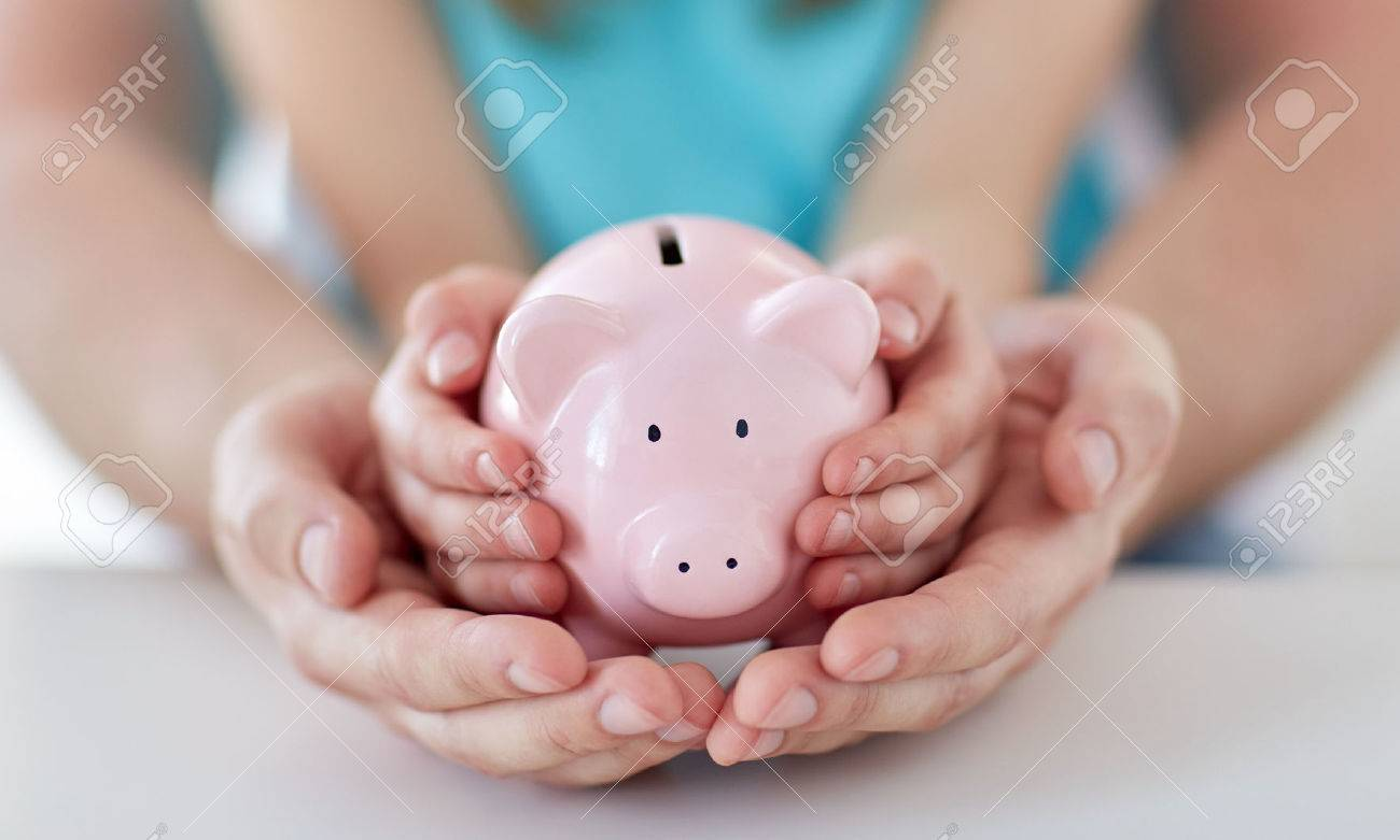 family, children, money, investments and people concept - close up of father and daughter hands holding pink piggy bank - 38662892