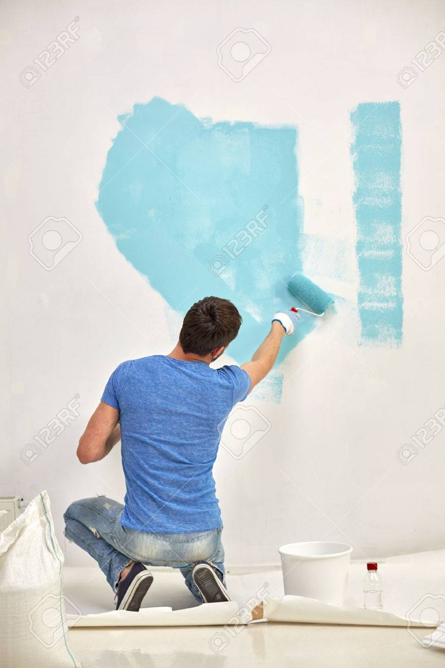Person painting wall - Repair Building People And Renovation Concept Man With Roller Painting Wall In Blue