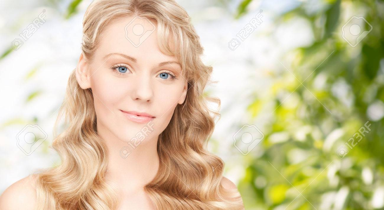 beauty, people, hair care and health concept - beautiful young woman face with long wavy hair over green background - 38879971