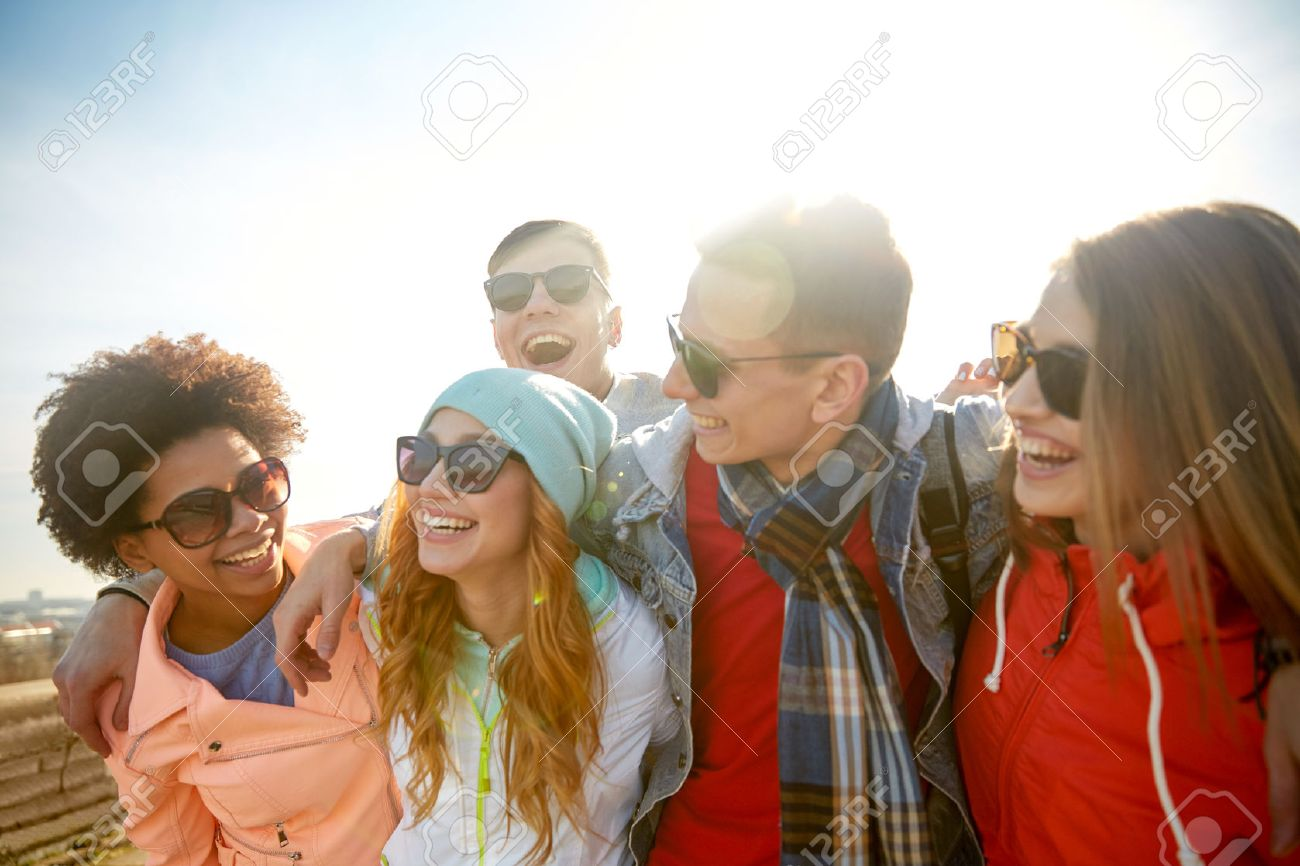 tourism, travel, people, leisure and teenage concept - group of happy friends in sunglasses hugging and laughing on city street Stock Photo - 45879228