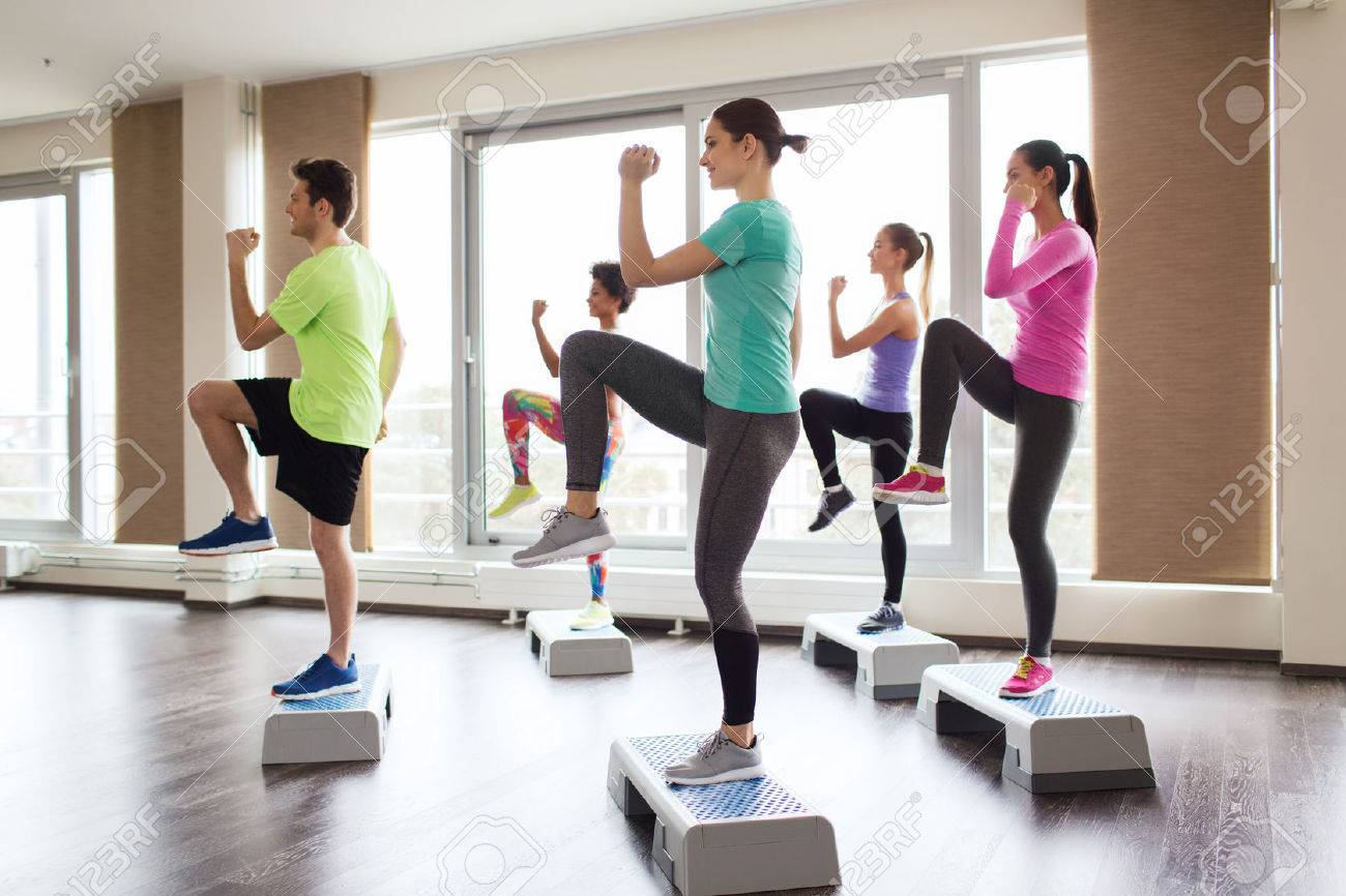 fitness, sport, training, aerobics and people concept - group of people working out with steppers in gym - 45880749
