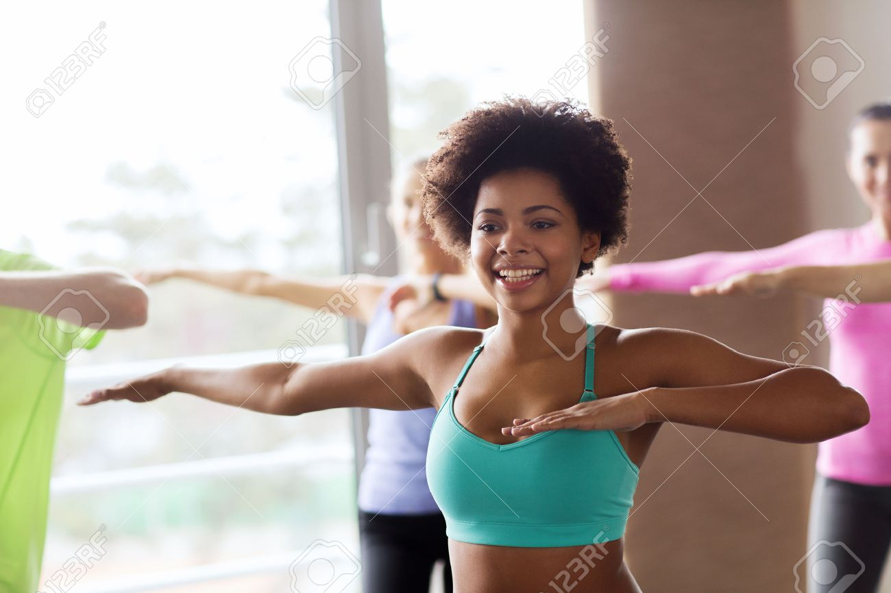 fitness, sport, dance and lifestyle concept - group of smiling people with coach dancing zumba in gym or studio Stock Photo - 45880763
