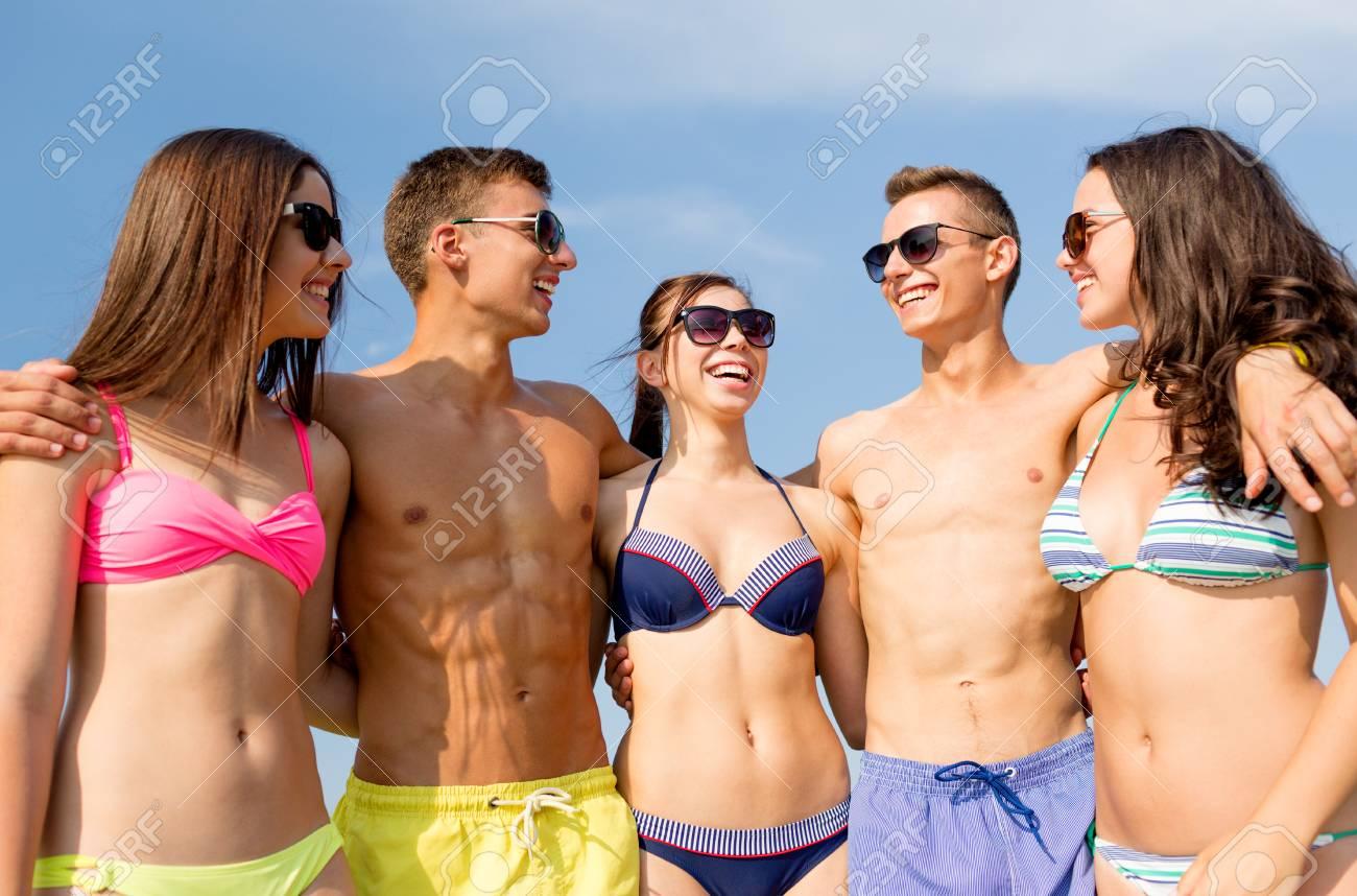 9dfaa8742ce3 Grupo de amigos sonrientes que usan trajes de baño y gafas de sol hablando  y riendo en la playa