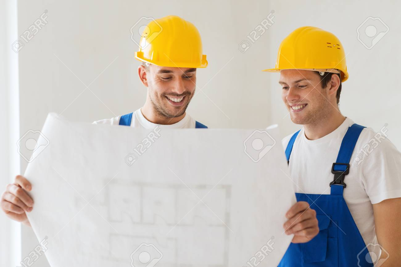 Building teamwork and people concept group of smiling builders building teamwork and people concept group of smiling builders in hardhats with blueprint indoors malvernweather Images