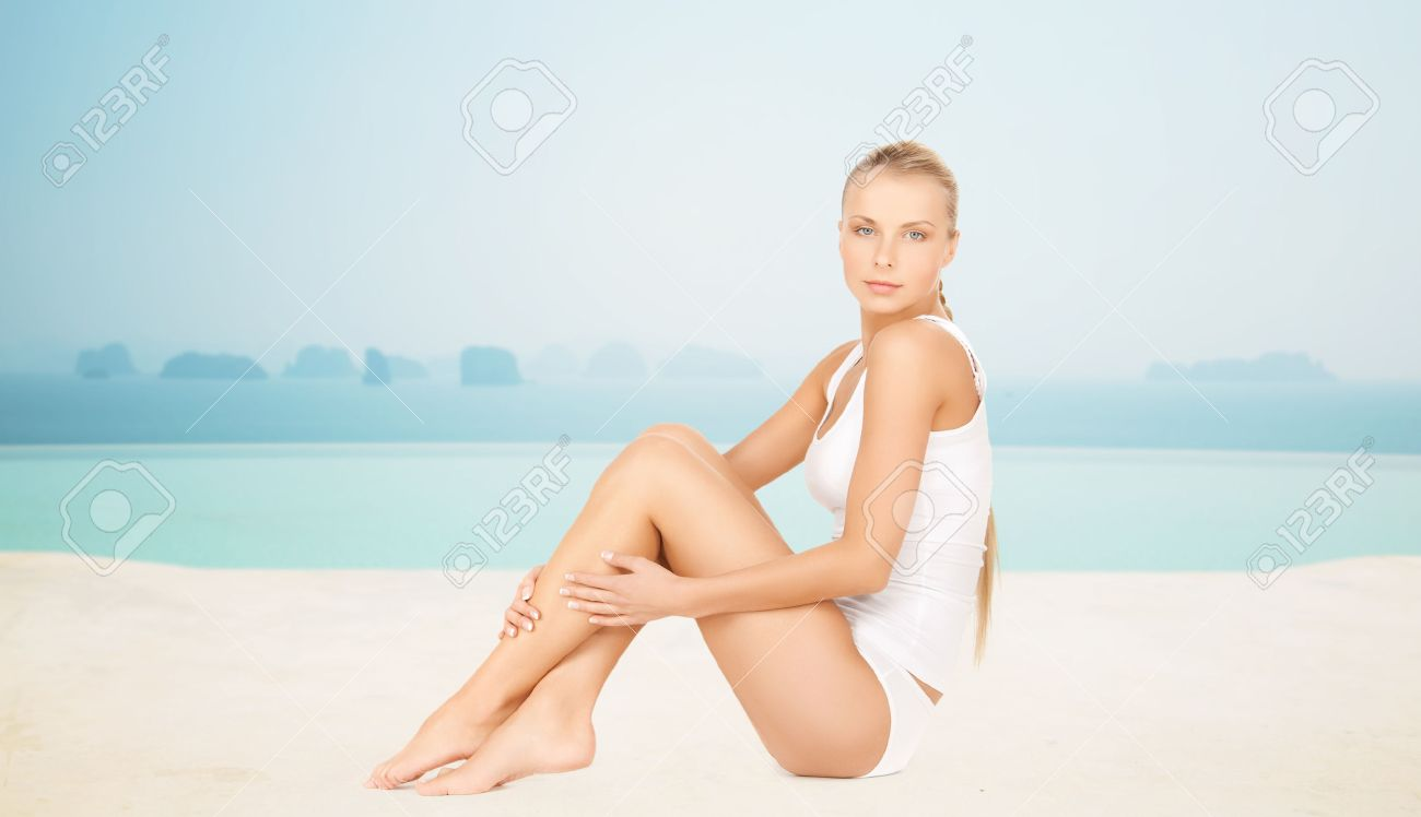 people, beauty, spa and resort concept - beautiful woman in cotton underwear over infinity edge pool background Stock Photo - 47510567