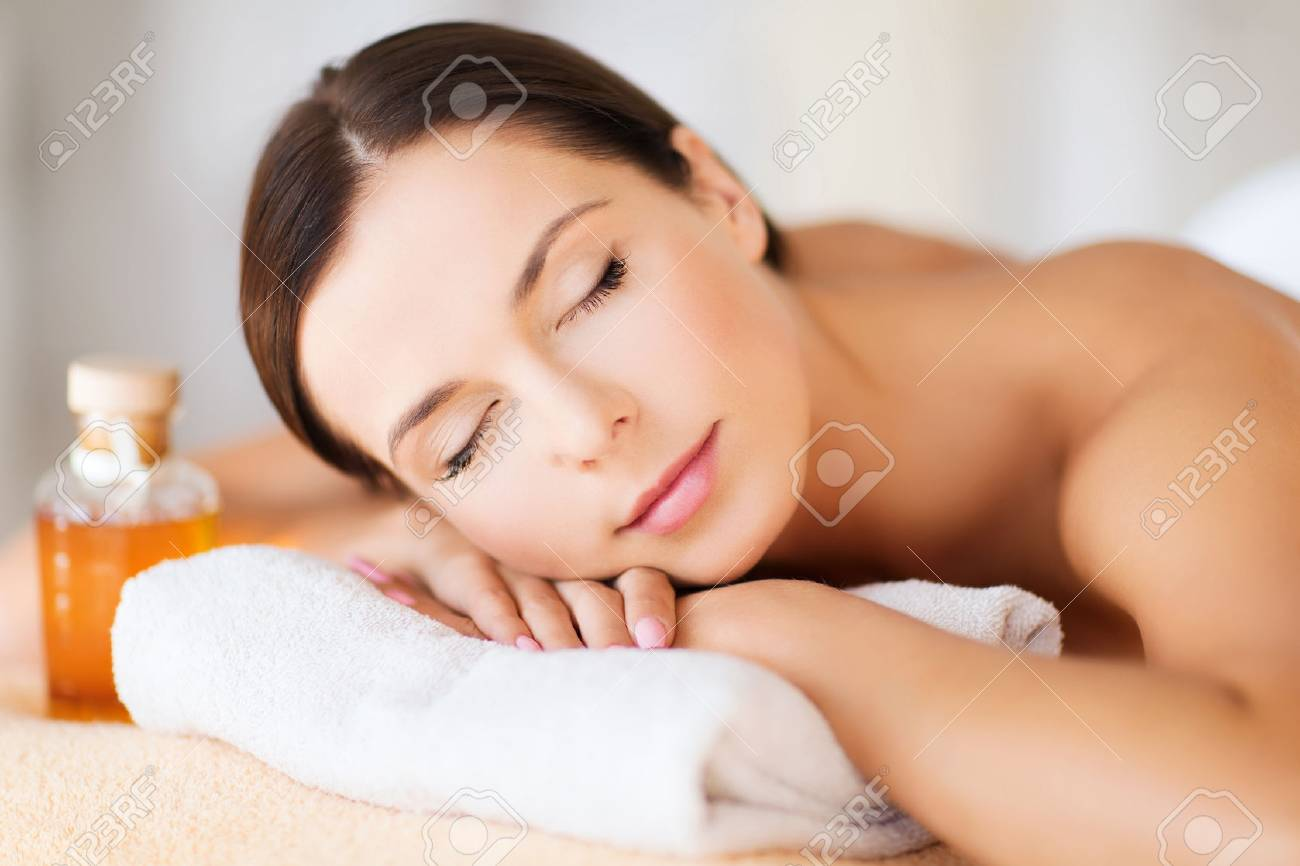 beauty and spa concept - happy woman in spa salon lying on the massage desk Stock Photo - 47564203