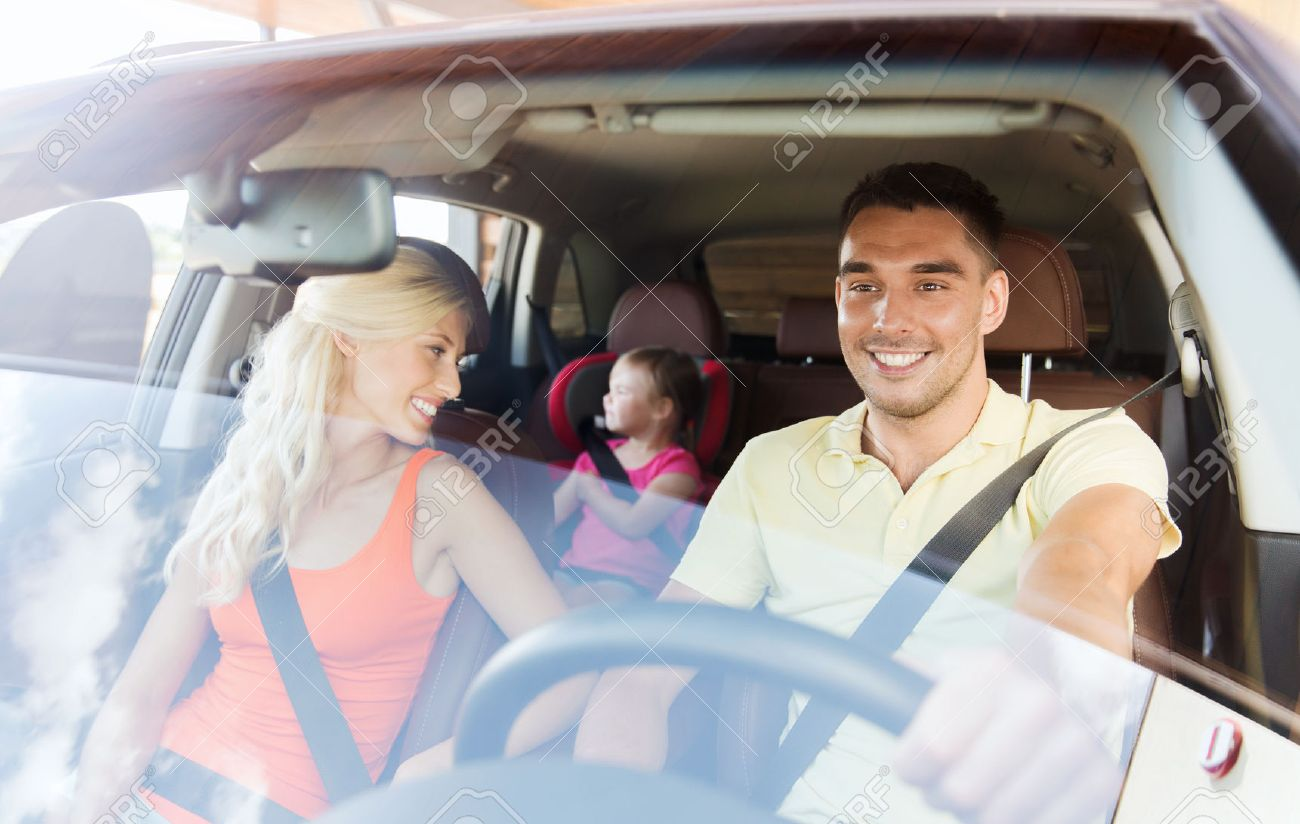 family, transport, safety, road trip and people concept - happy man and woman with little child driving in car Stock Photo - 47872653
