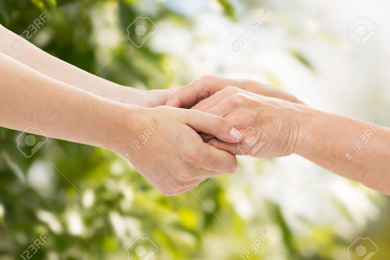 people, age, family, care and support concept - close up of senior woman and young woman holding hands over green natural background - 48511436