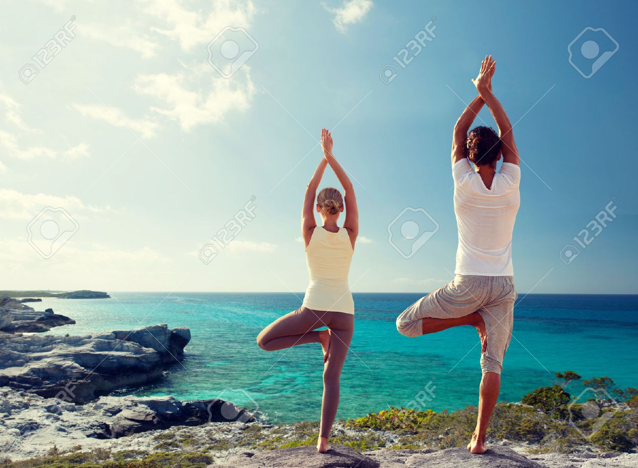 fitness, sport, and lifestyle concept - couple making yoga exercises on beach from back - 48512610