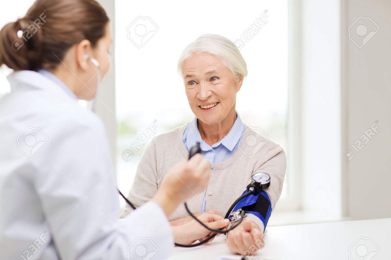 medicine, age, health care and people concept - doctor with tonometer checking happy senior woman blood pressure level at hospital - 48507398