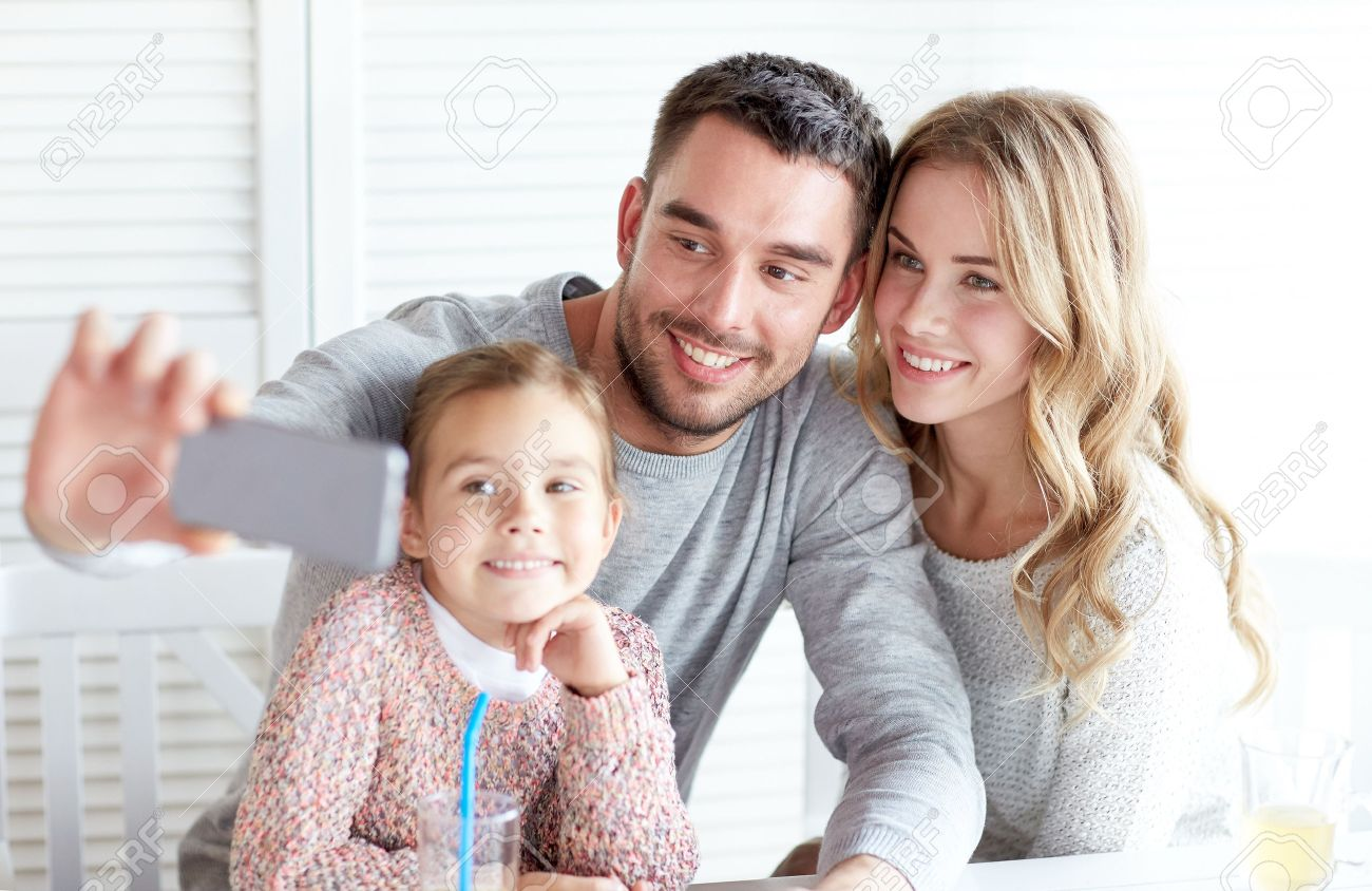 family, parenthood, technology and people concept - happy mother, father and little girl having dinner and taking selfie by smartphone at restaurant - 48790158