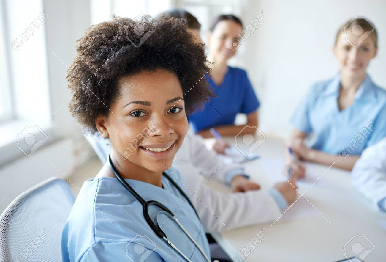 health care, profession, people and medicine concept - happy african american female doctor or nurse over group of medics meeting at hospital Stock Photo - 49162809