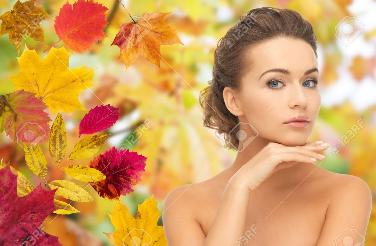 beauty, people, season and health concept - beautiful young woman touching her face over autumn leaves background Stock Photo - 49278900