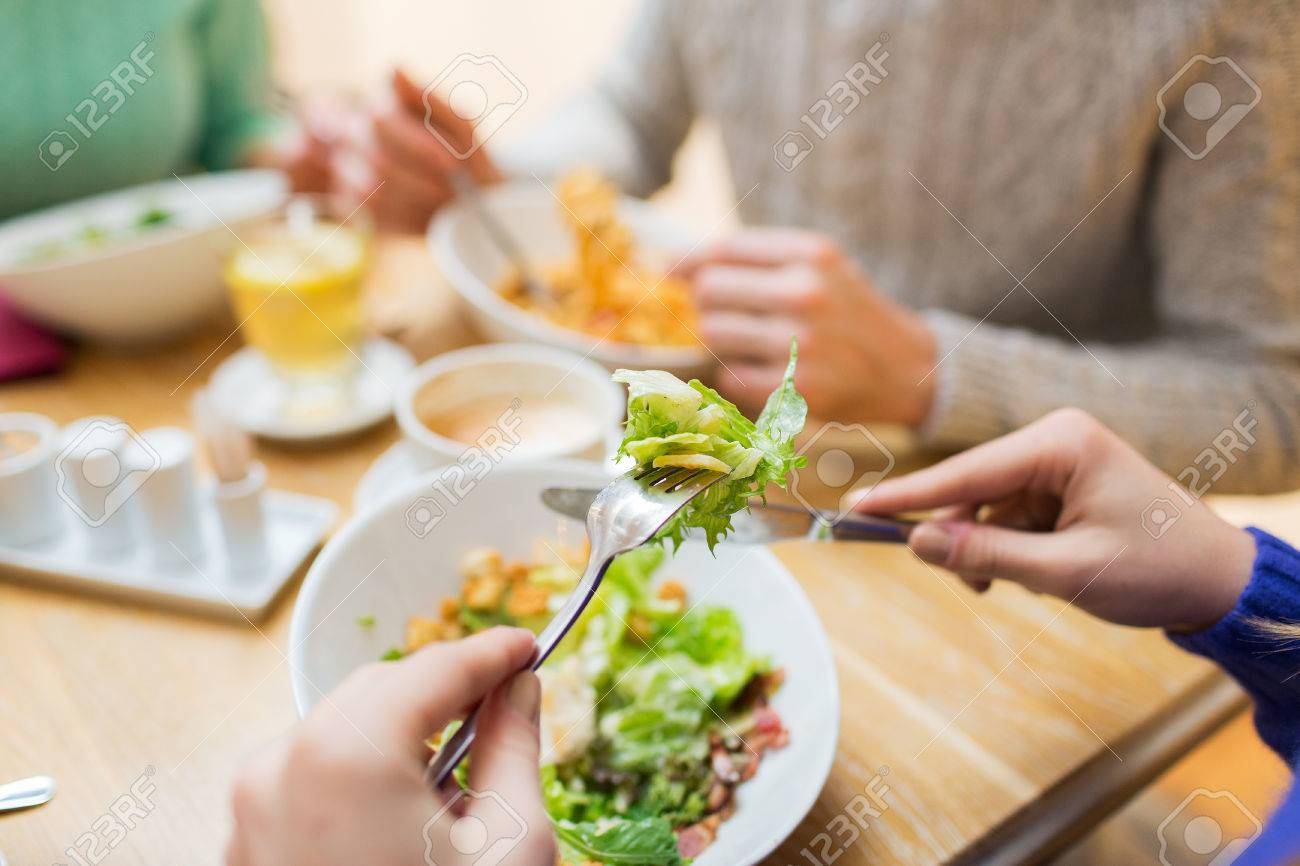 people, leisure and food concept - close up friends having dinner and eating at restaurant - 49308544