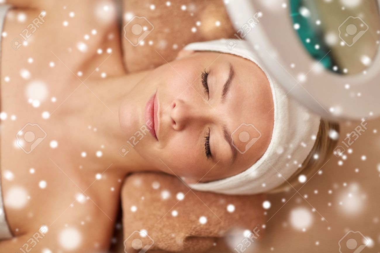 people, beauty, skin care, winter and relaxation concept - close up of beautiful young woman face with closed eyes under magnifying lamp in spa salon with snow effect - 50052211