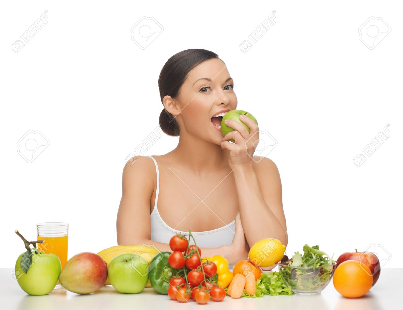 woman eating apple with lot of fruits and vegetables - 50154806