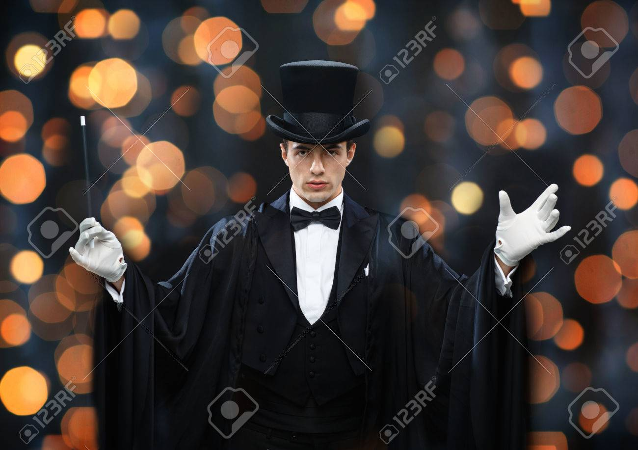 performance, circus, show concept - magician in top hat and cape showing trick with magic wand over nigh lights background - 50184918