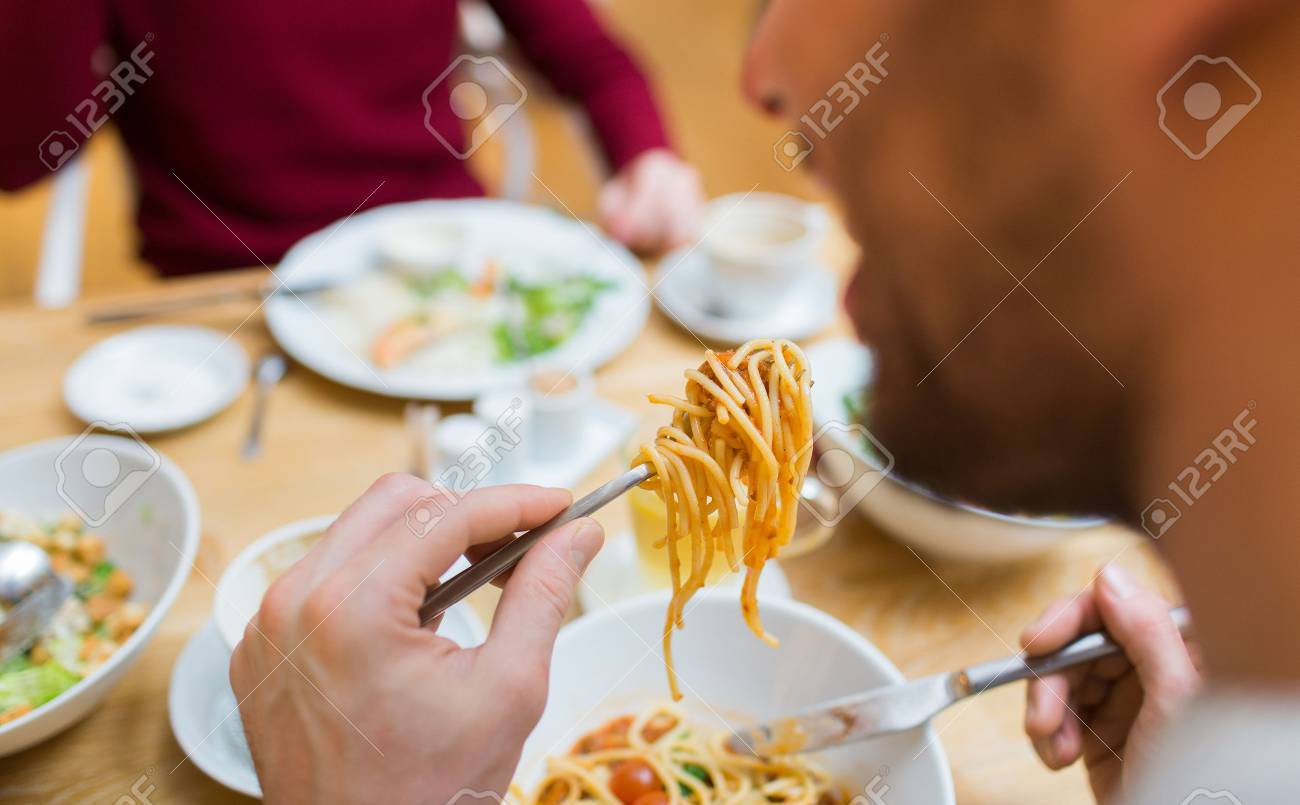 people, leisure and food concept - close up man eating pasta for dinner at restaurant or home - 50278031