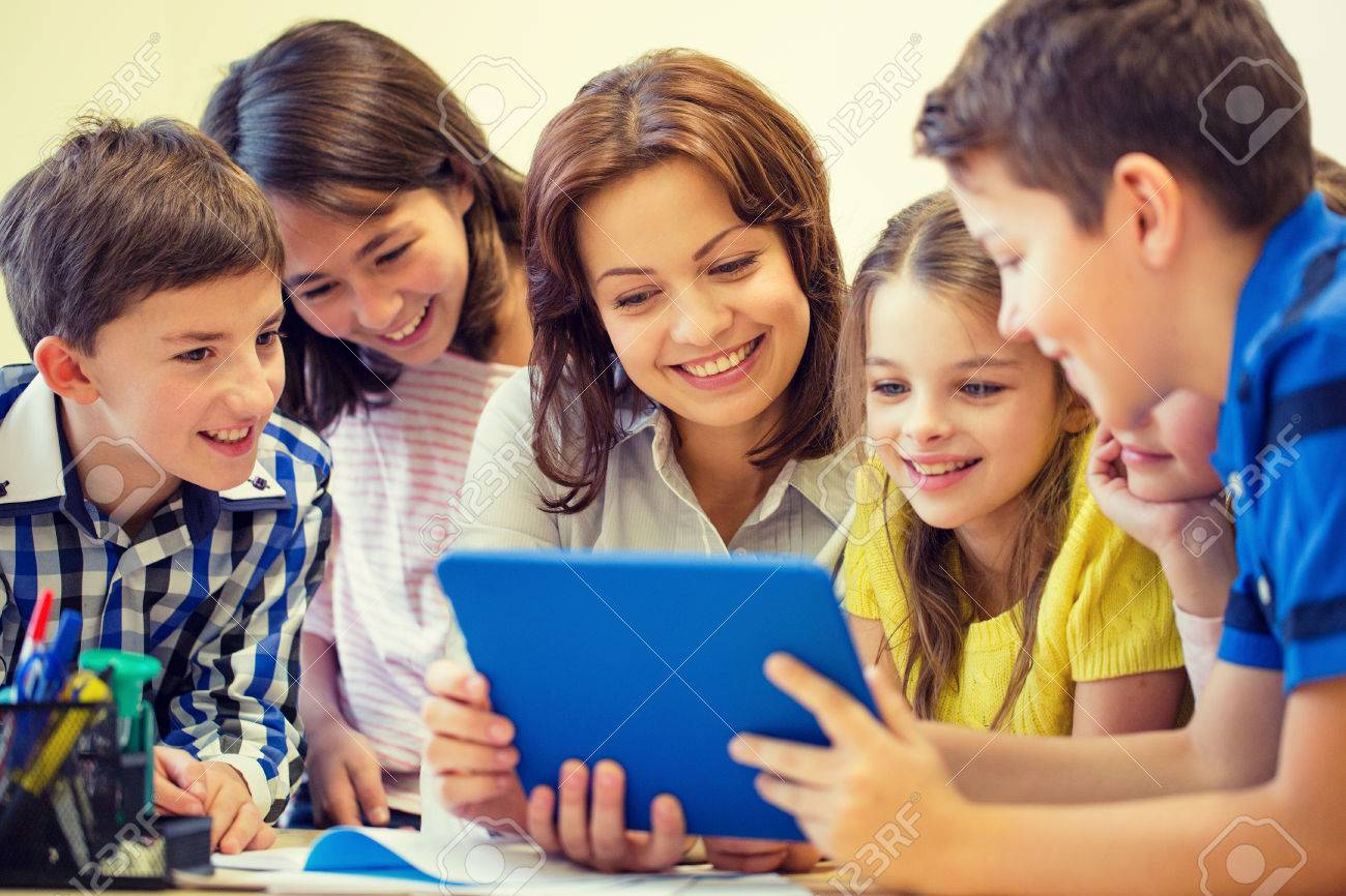 education, elementary school, learning, technology and people concept - group of school kids with teacher looking to tablet pc computer in classroom - 50369459