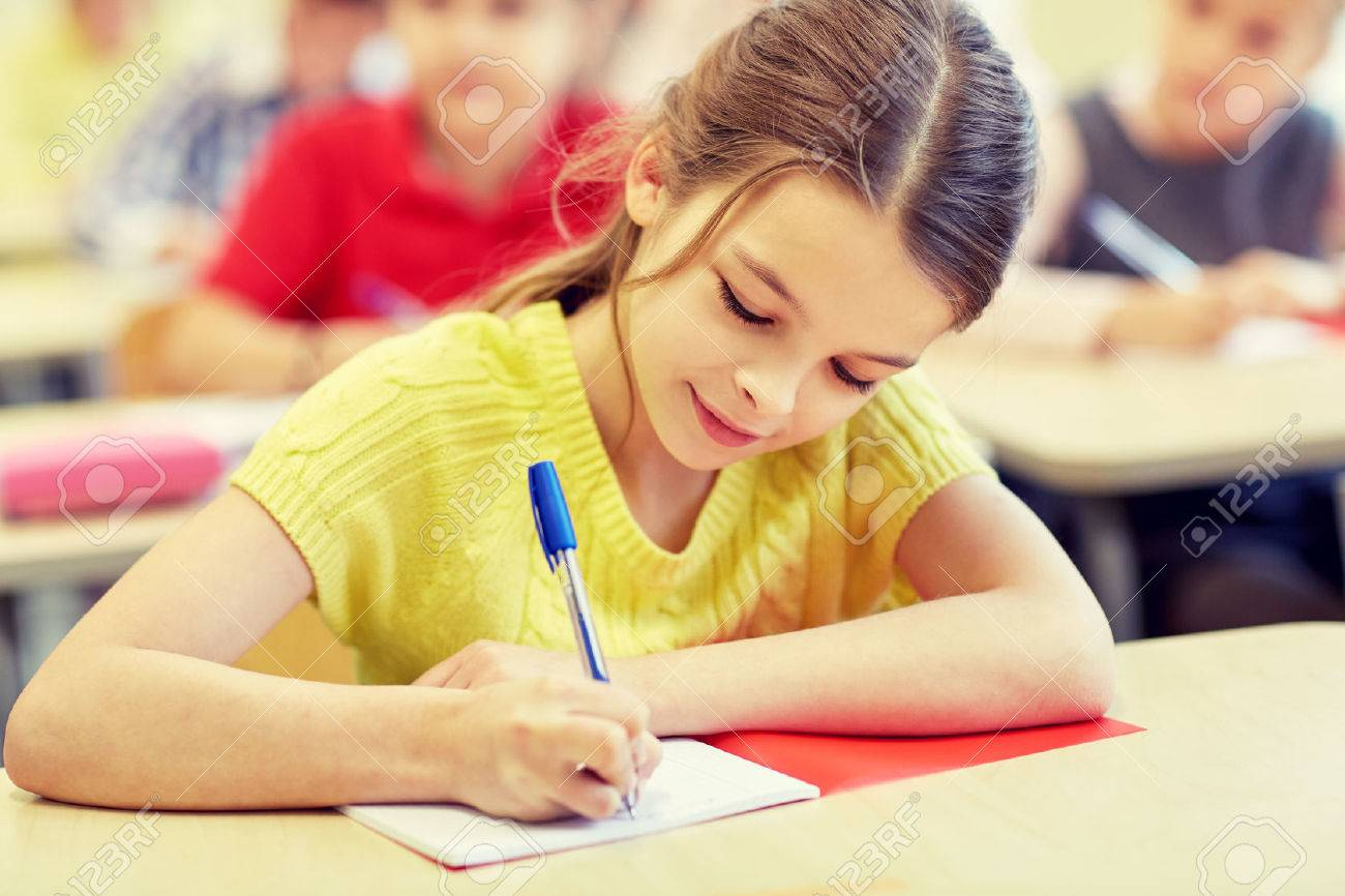 education, elementary school, learning and people concept - group of school kids with pens and notebooks writing test in classroom - 50369465