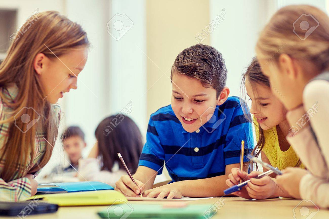 education, elementary school, learning and people concept - group of school kids with pens and papers writing in classroom - 50369537