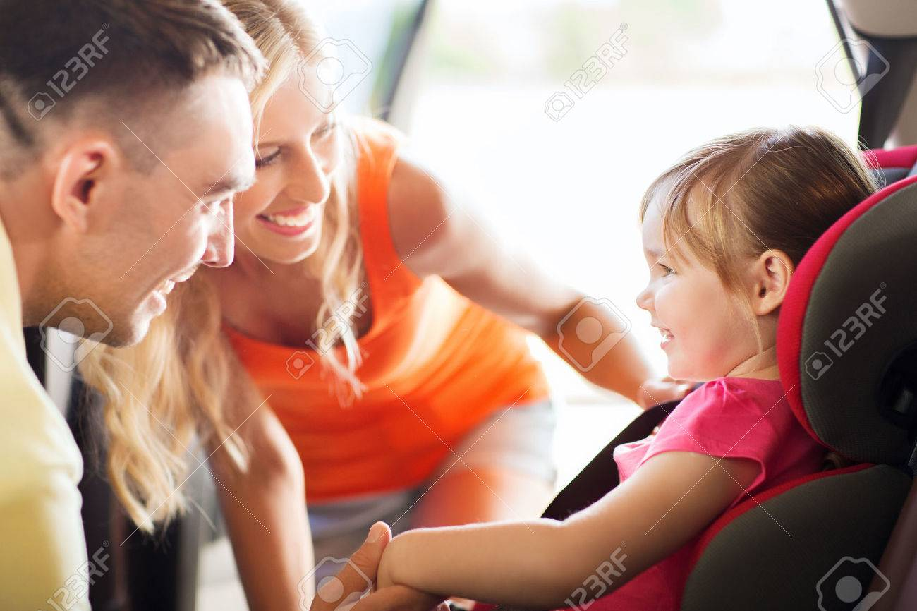 family, transport, safety, road trip and people concept - happy parents talking to little girl in baby car seat - 50370378