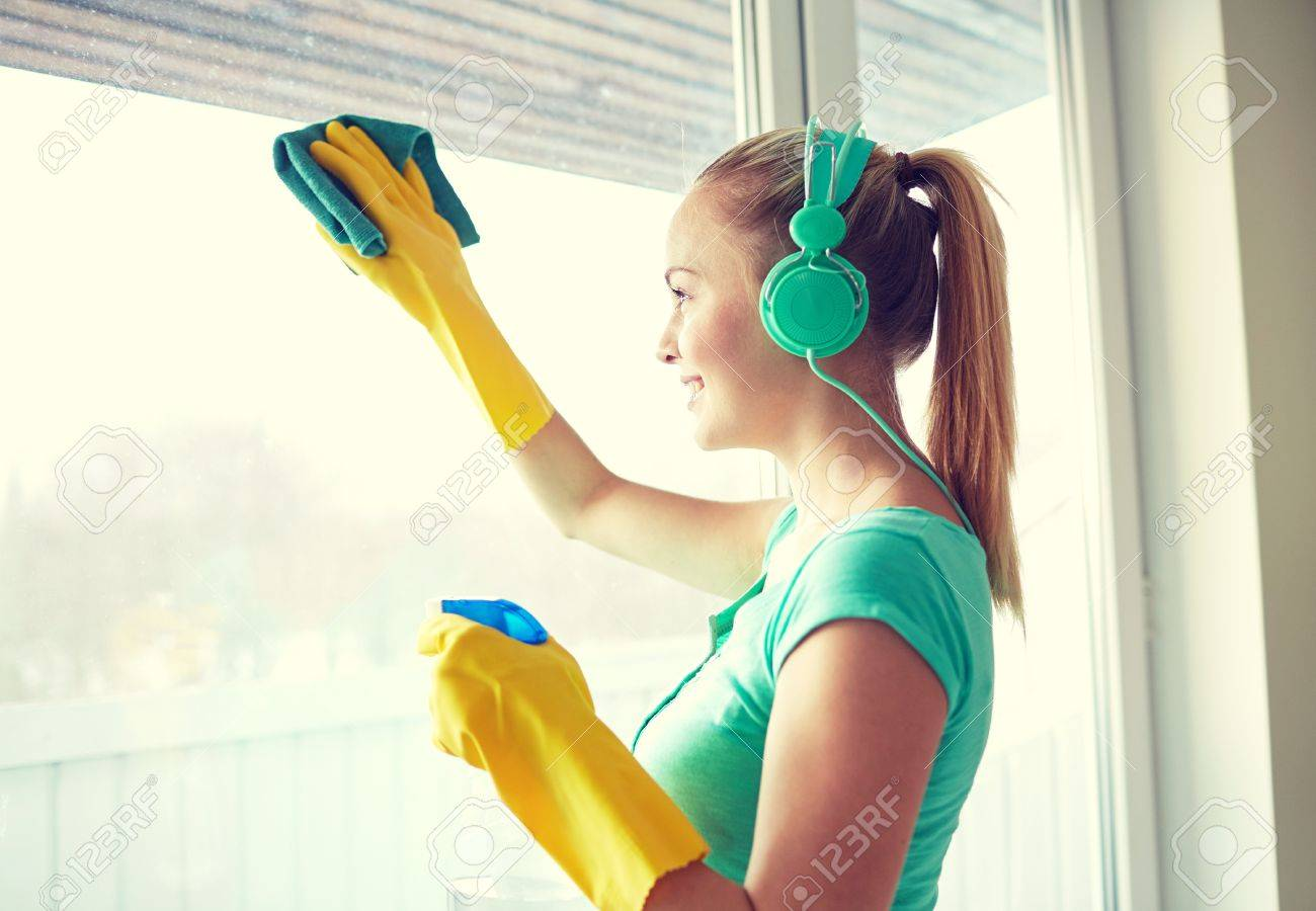 people, housework and housekeeping concept - happy woman in headphones listening to music and cleaning window with cleanser at home - 50685635