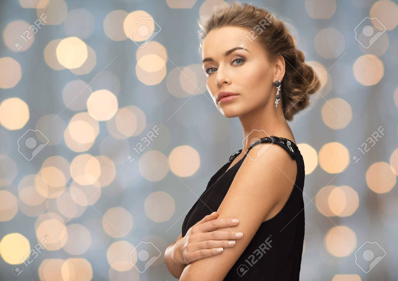 people, holidays and glamour concept - beautiful woman wearing earrings over lights background - 50589491