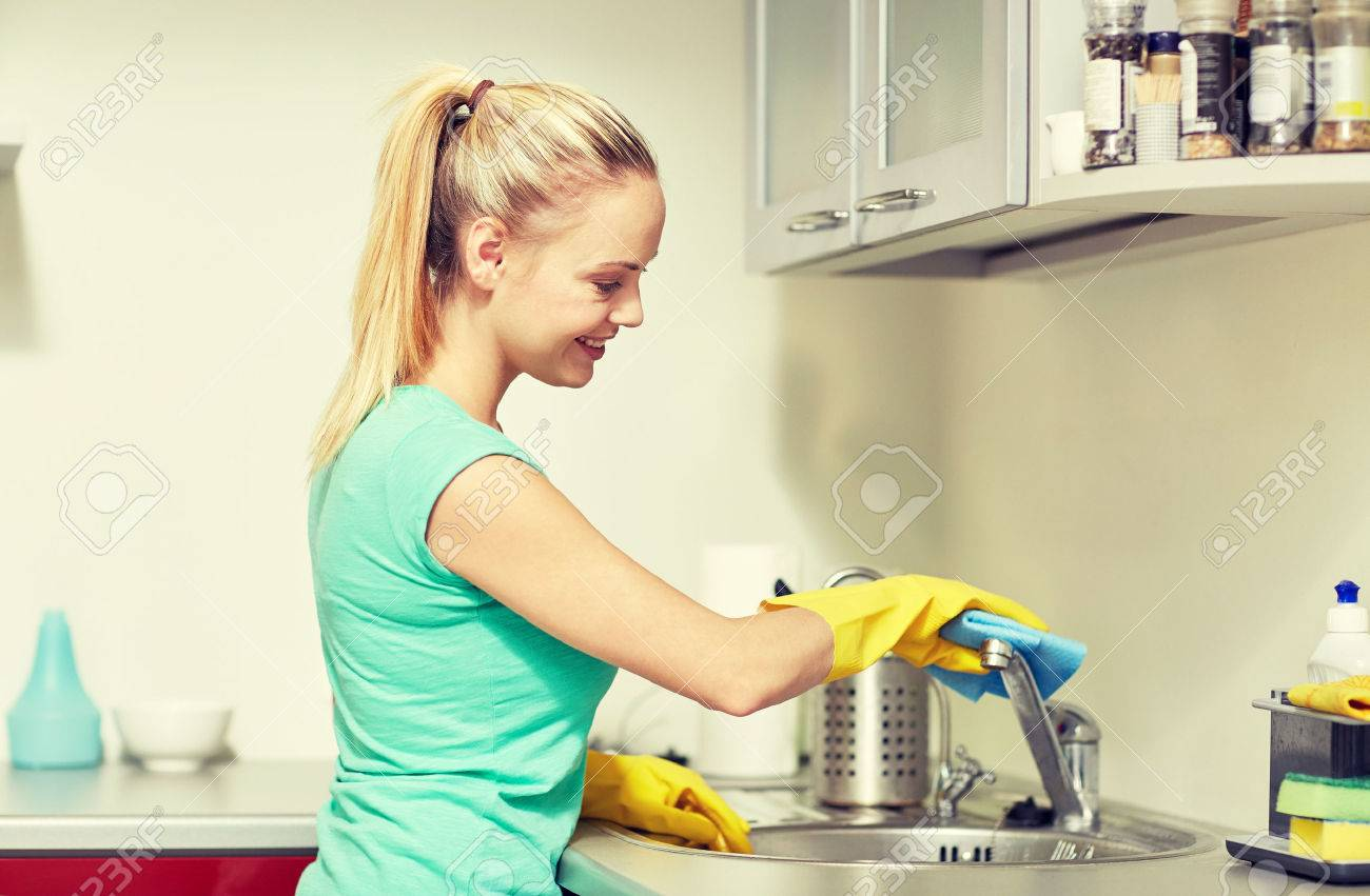 people, housework and housekeeping concept - happy woman in protective gloves cleaning tap with rag at home kitchen - 50944546