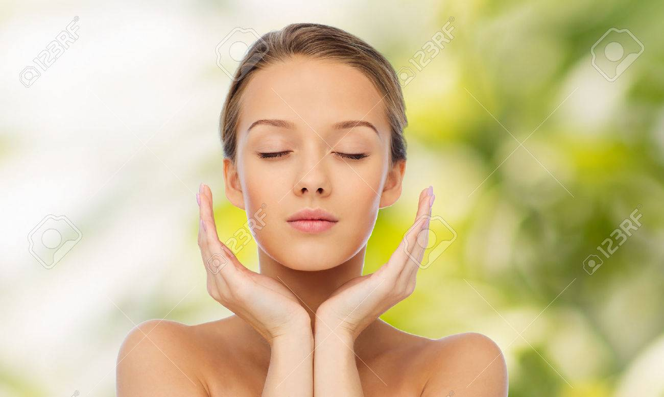 beauty, people, skincare and health concept - young woman face and hands over green natural background - 51023721
