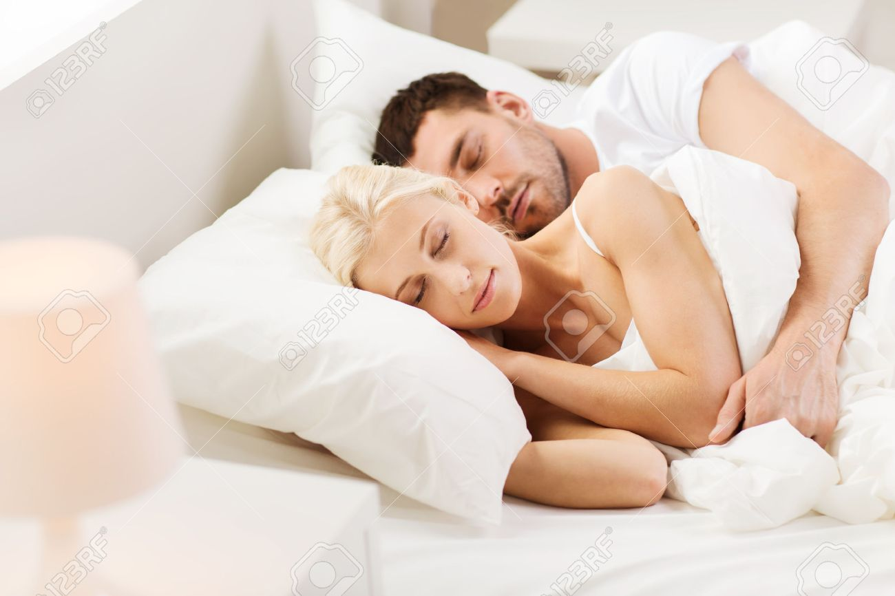 people, family, bedtime and happiness concept - happy couple sleeping and hugging in bed at home Stock Photo - 51023576
