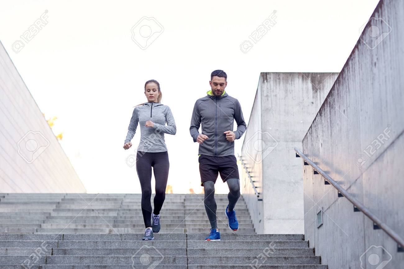 fitness, sport, exercising, people and lifestyle concept - couple walking downstairs on stadium Stock Photo - 51023560