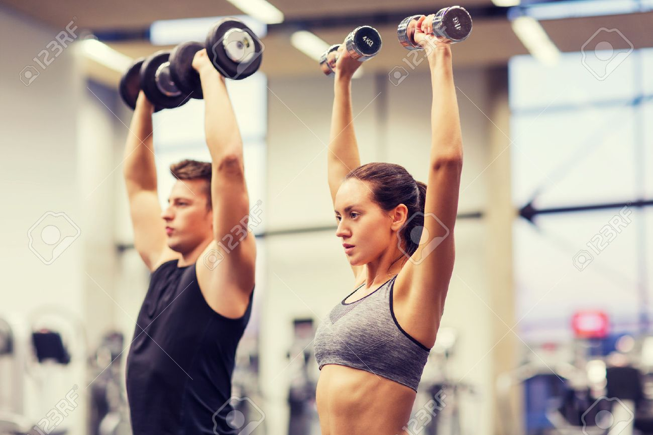 sport, fitness, lifestyle and people concept - smiling man and woman with dumbbells flexing muscles in gym - 51225304