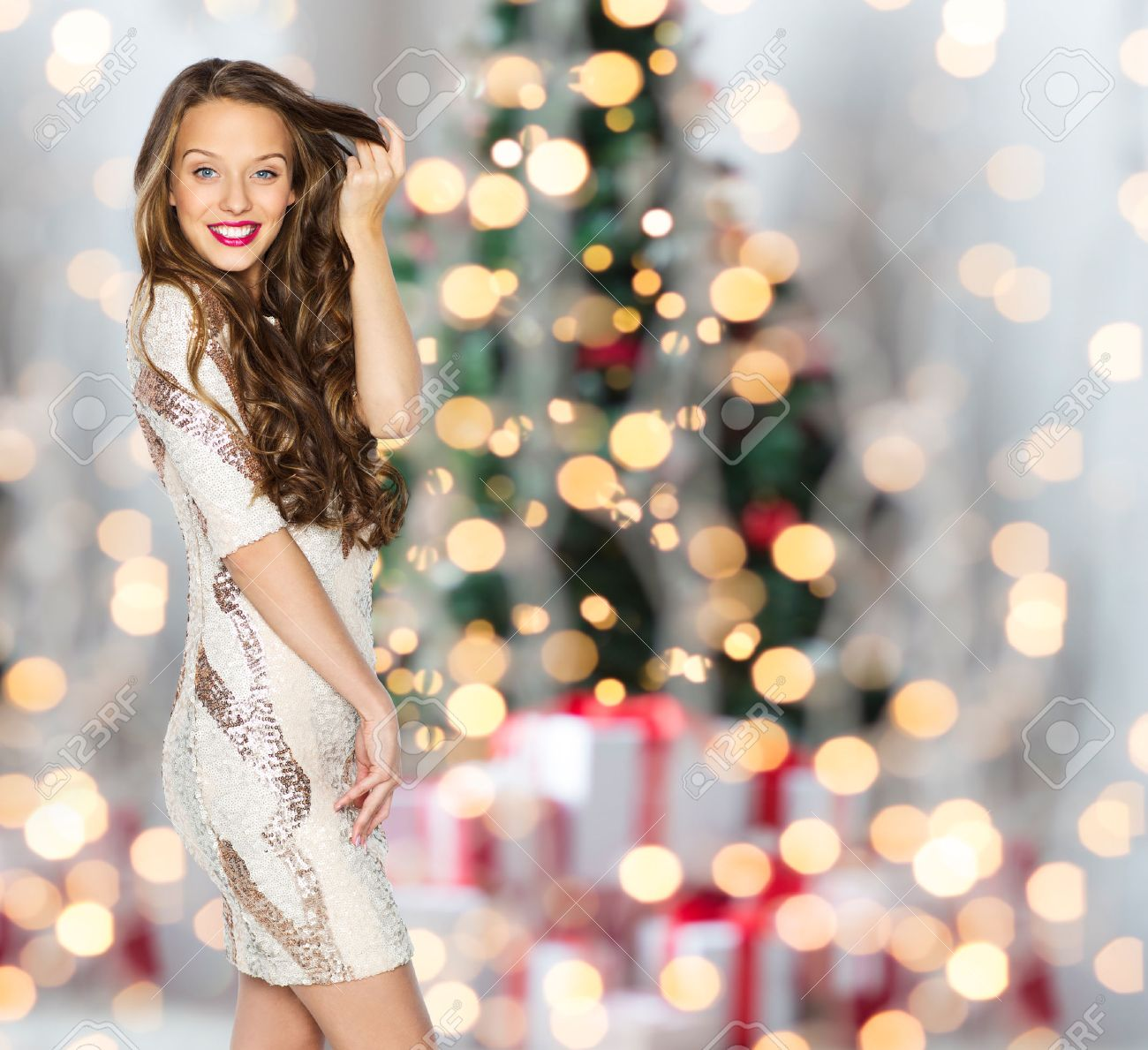 people, holidays, hairstyle and fashion concept - happy young woman or teen girl in fancy dress with sequins touching long wavy hair over christmas tree lights background - 51225833