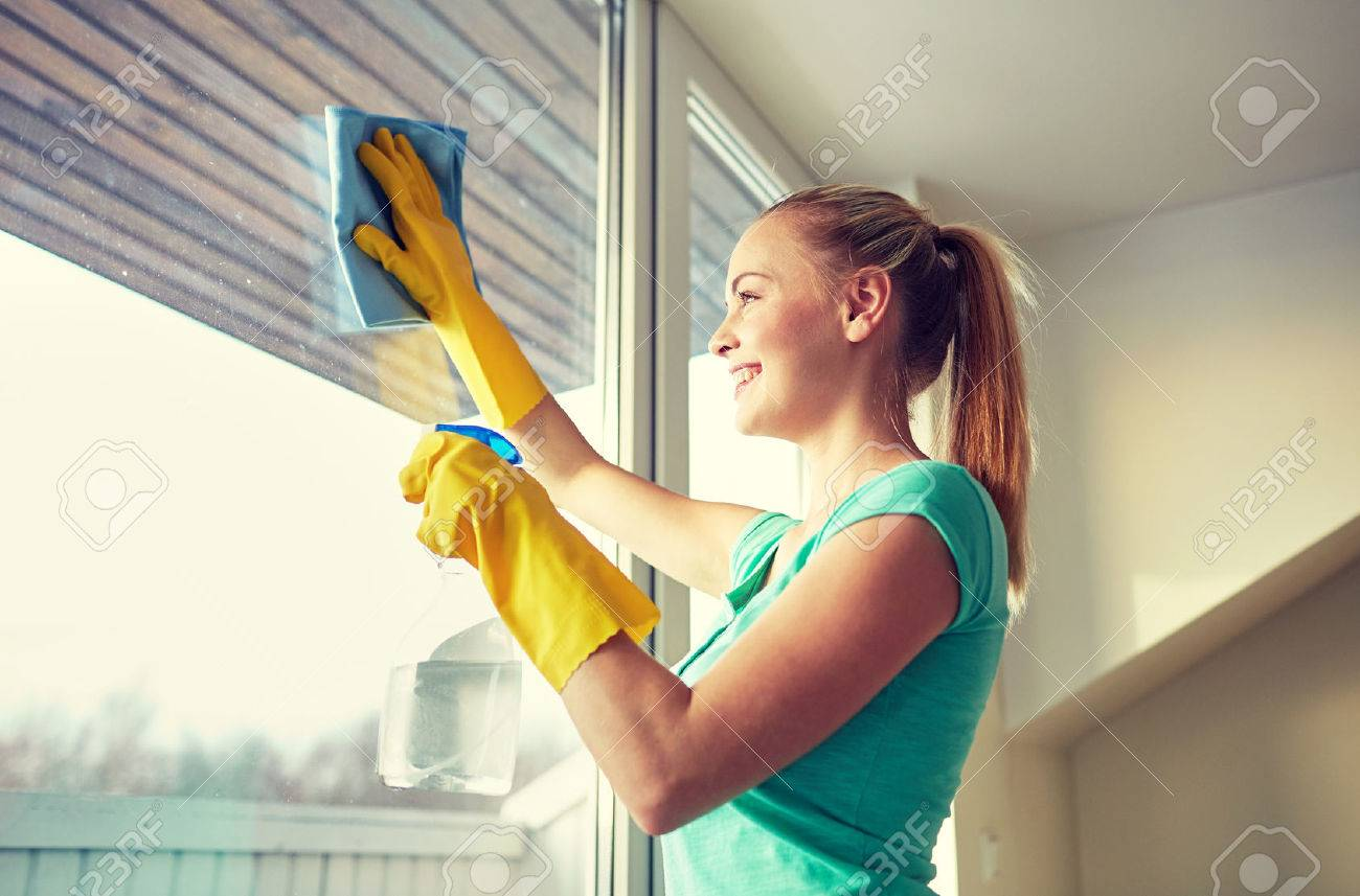 people, housework and housekeeping concept - happy woman in gloves cleaning window with rag and cleanser spray at home - 51129854