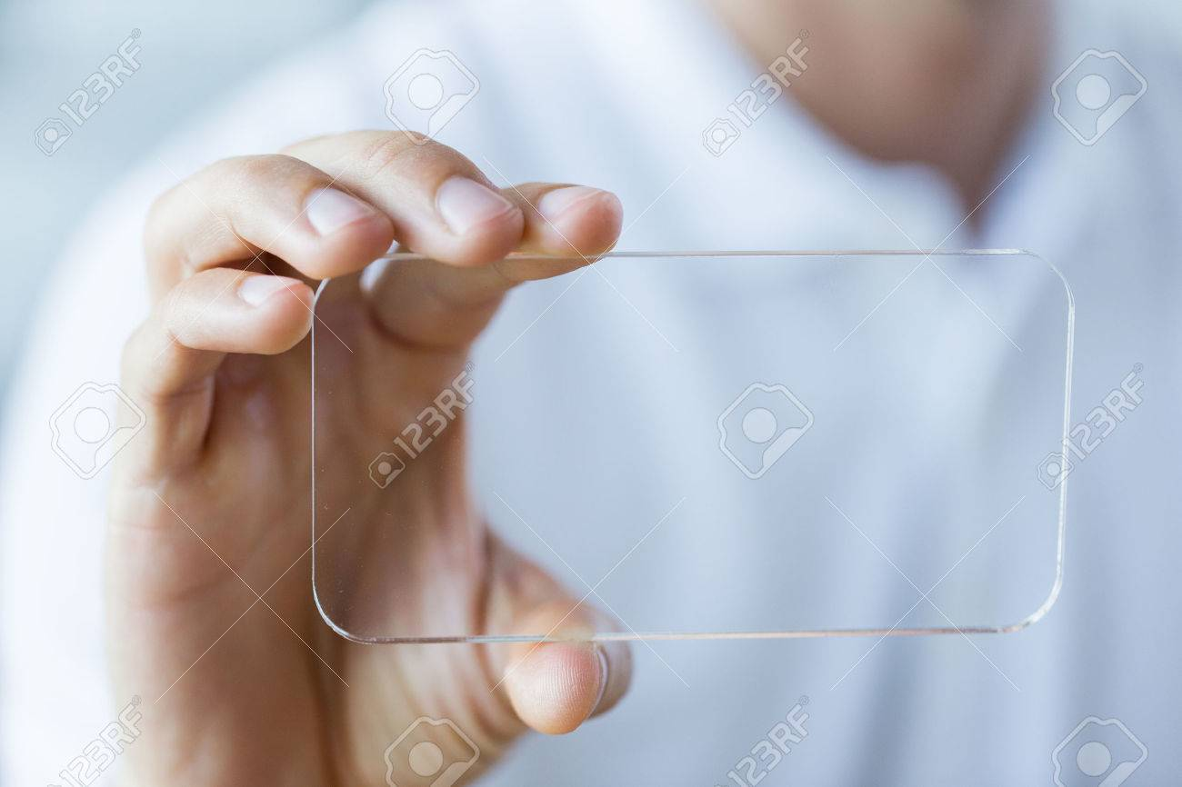 business, technology and people concept - close up of male hand holding and showing transparent smartphone at office Stock Photo - 51238228