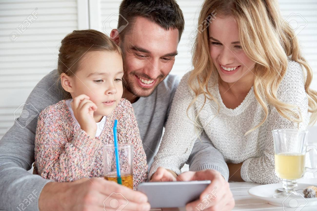 family, parenthood, technology and people concept - happy mother, father and little girl with smartphone having dinner at restaurant - 51334603