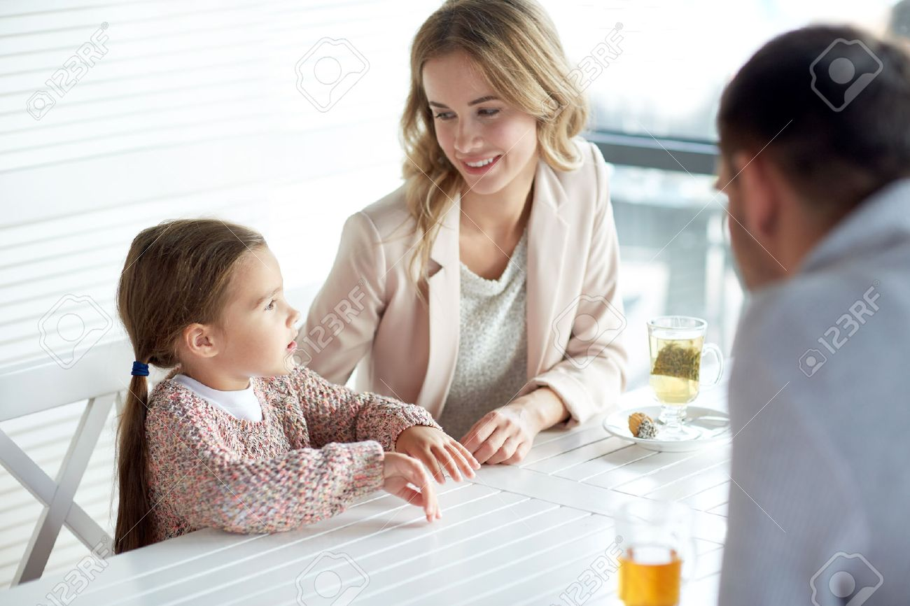 family, parenthood, communication and people concept - happy mother, father and little girl having dinner and talking at restaurant or cafe - 51334621