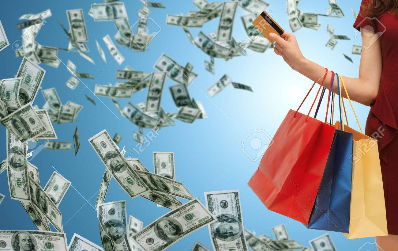 people, sale, finance and consumerism concept - close up of woman with shopping bags and bank or credit card over blue background and money rain - 51384983