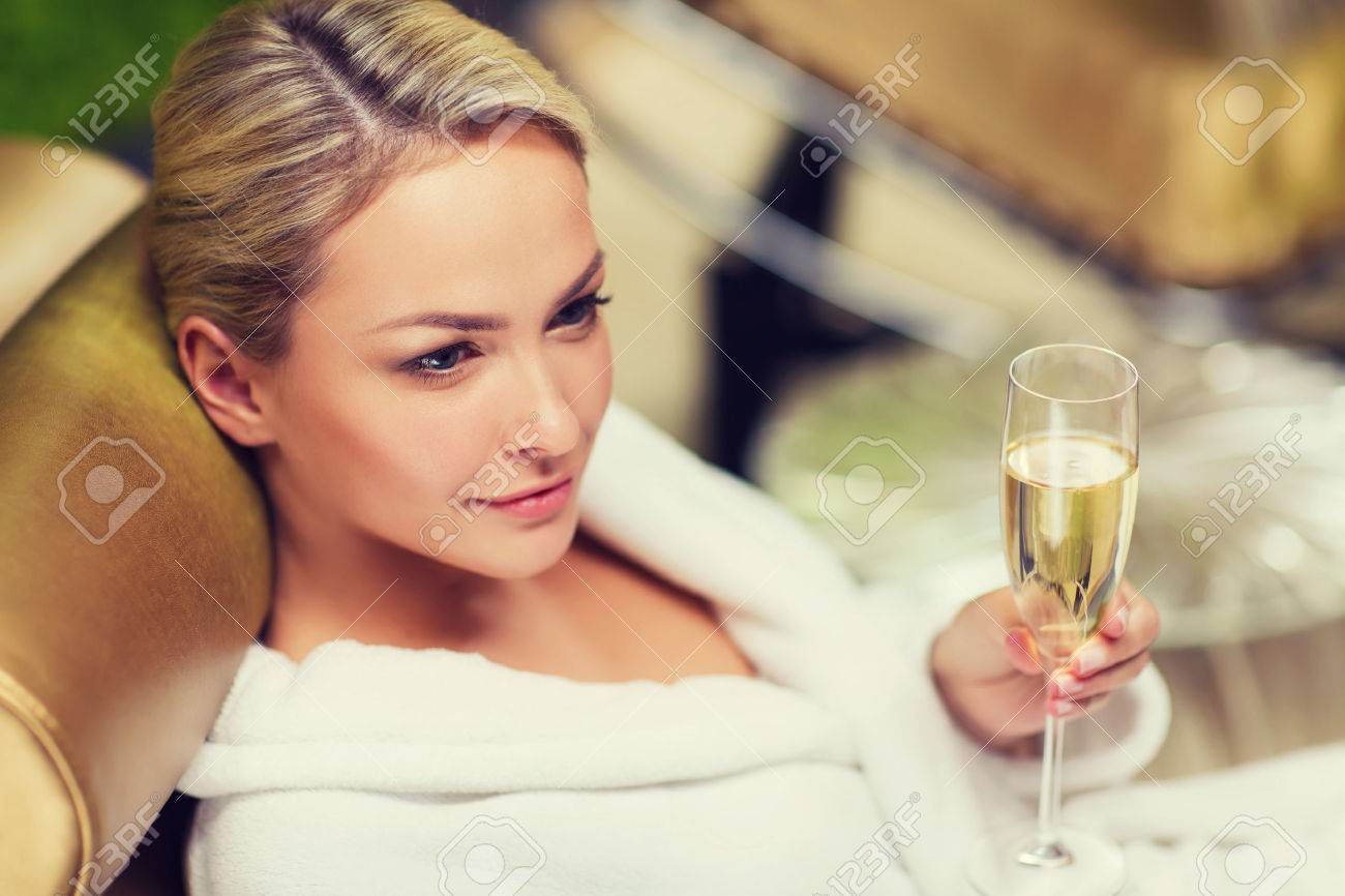 beautiful young woman in white bath robe lying on chaise-longue and drinking champagne at spa Stock Photo - 51809943