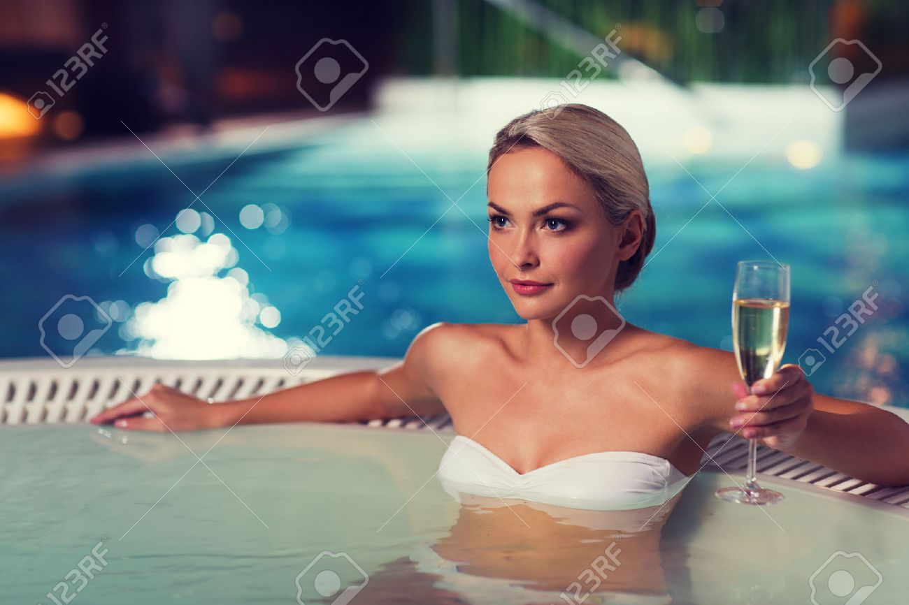 beautiful young woman wearing bikini swimsuit sitting with glass of champagne in jacuzzi at poolside Stock Photo - 51809947