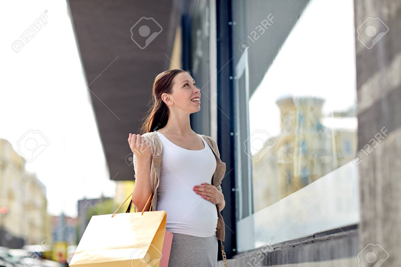 pregnancy, motherhood, people and expectation concept - happy smiling pregnant woman with shopping bags at city street - 51942255