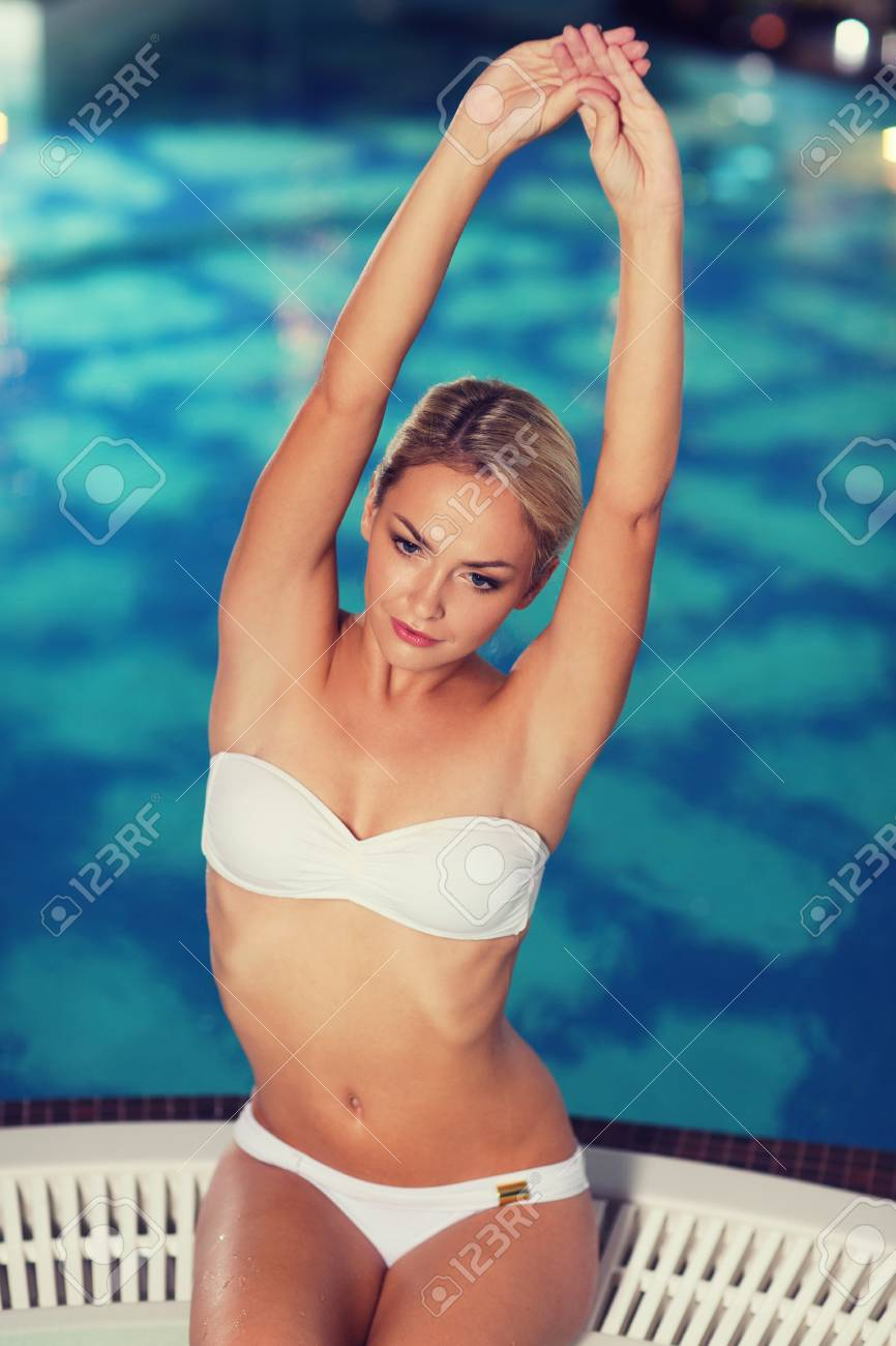 8bd9fb4e2313 Gente, belleza, spa, estilo de vida saludable y el concepto de relajación -  hermosa mujer joven con traje de baño bikini sentada con las manos ...