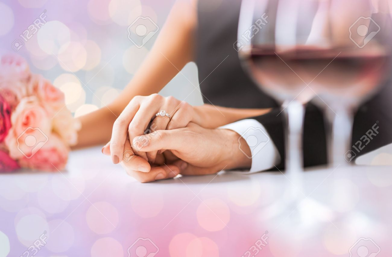 people, holidays, engagement and love concept - engaged couple holding hands with diamond ring over holidays lights background - 52118380