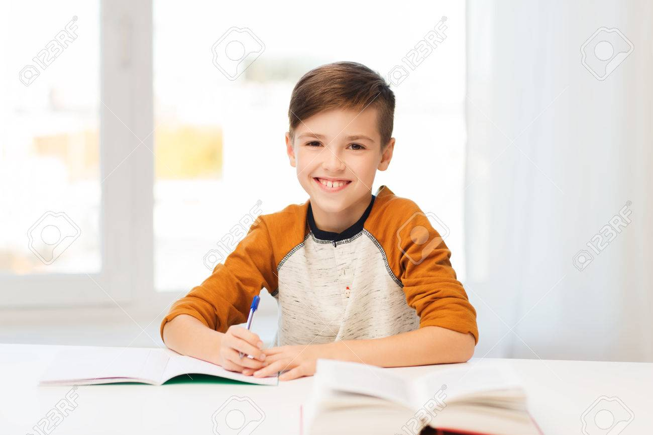 education, childhood, people, homework and school concept - smiling student boy with book writing to notebook at home - 52194633