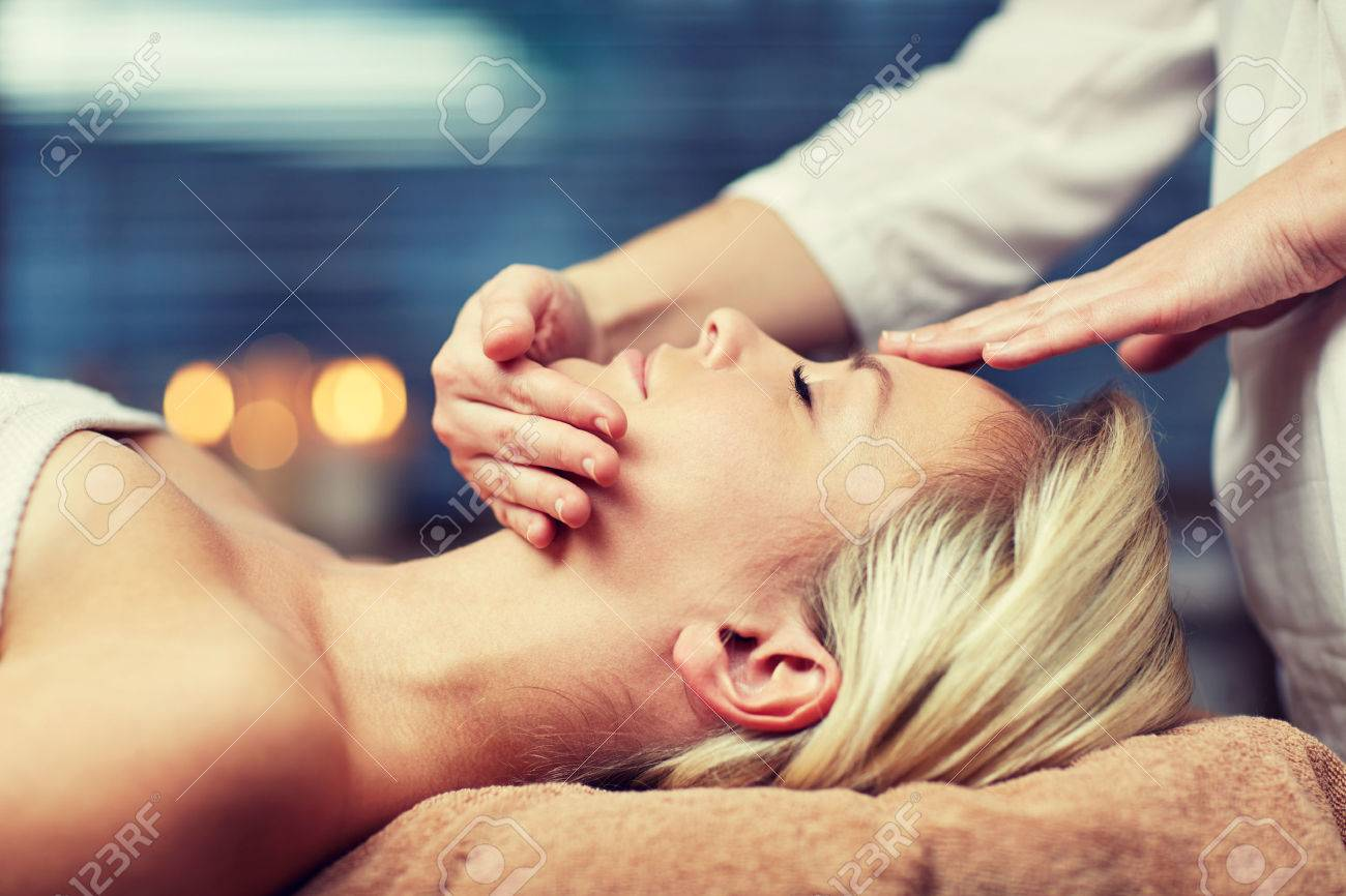 people, beauty, spa, healthy lifestyle and relaxation concept - close up of beautiful young woman lying with closed eyes and having face or head massage in spa - 52767449