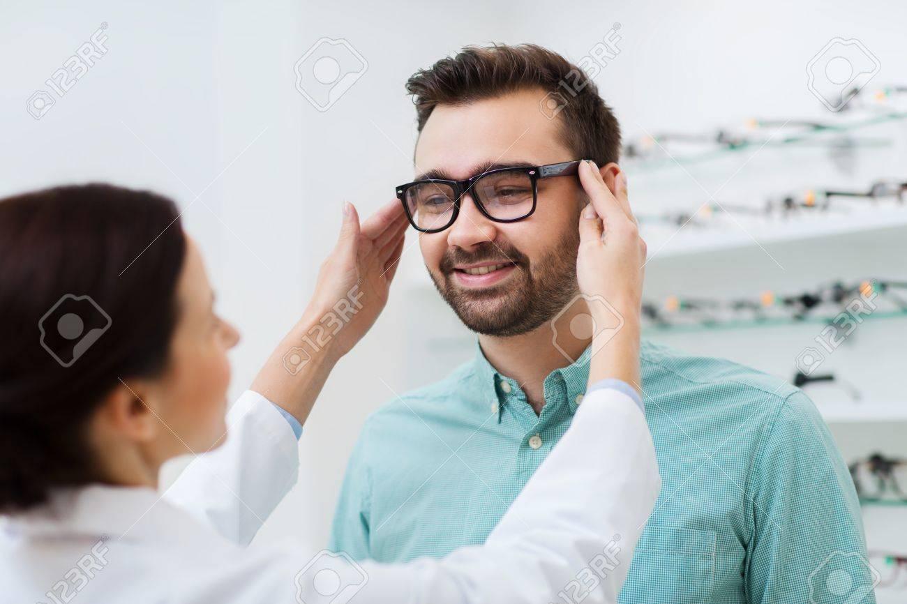 meilleur endroit pour magasin Achat Soins de santé, les gens, la vue et le concept de vision - opticien femme  mettre des lunettes à l'homme au magasin d'optique