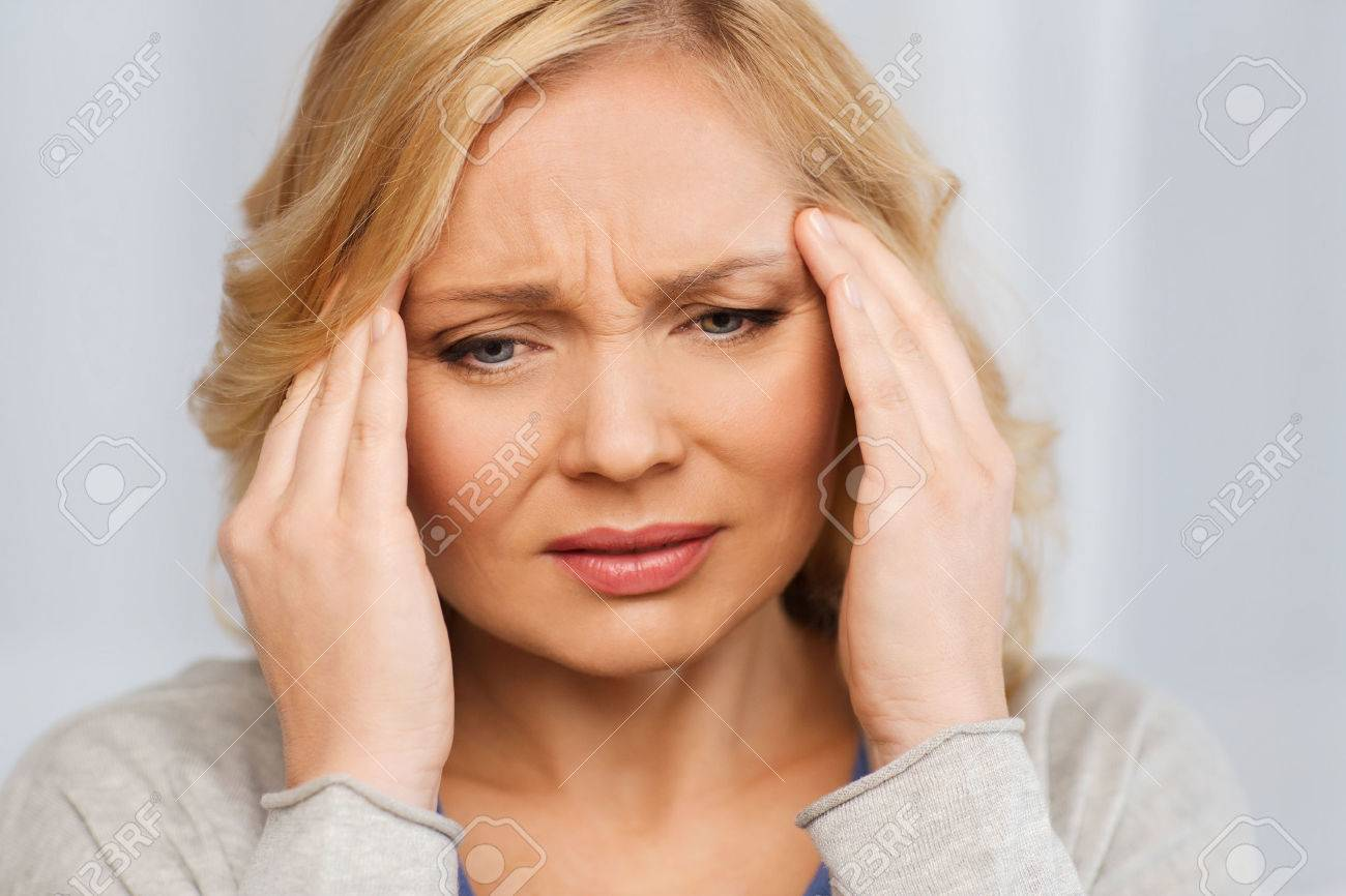 people, healthcare, stress and problem concept - unhappy woman suffering from headache at home - 52912796