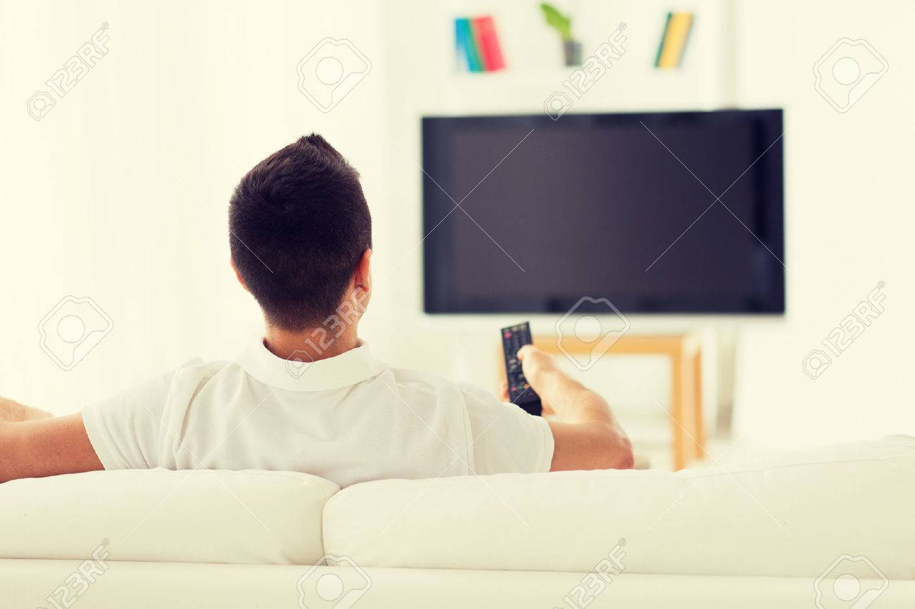 leisure, technology, mass media and people concept - man watching tv and changing channels at home from back - 52912878